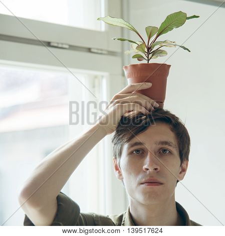 man keep a pot with plant on his head. ecological concept