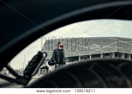 Portrait of a biker men with a beard in the leather jacket standing on the street and looking away. Picture made through motorcycle wheel.