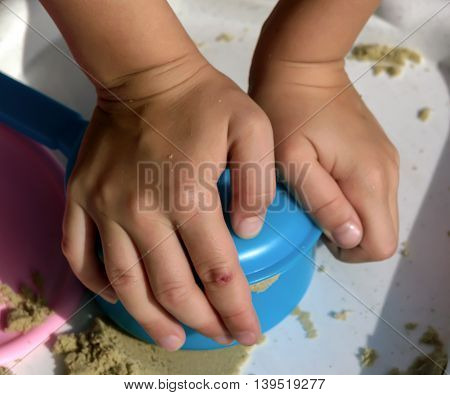 small hands of a child under school age out of the sand mold, blue baby dishes covered with a lid on it lie two palms pressed near pink plate