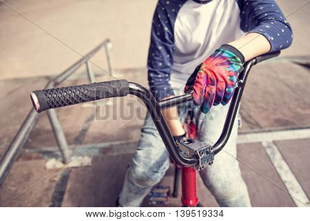 Young BMX rider boy sitting on a bicycle at the top of a ramp in skate park and holding her hand on a handlebar. Close up. Extreme sport. Youth lifestyle