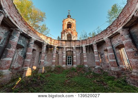 Ancient rotunda with columns without a dome on the bell tower of the background and blue sky at sunset. Abandoned brick temple overgrown with grass