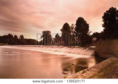 orange evening sunset photo with weir on the river Ohre in the village Hostenice in Ceske stredohori region in Czech republic