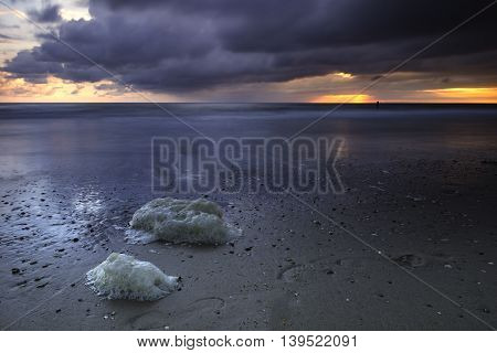 Long exposure photo of a beautiful coastline under storm clouds during sunset with in the foreground foam and footsteps.