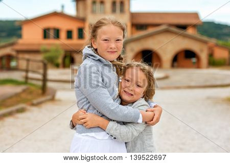 Two adorable kids playing outdoors on a very windy day. Image taken in Tuscany, Italy