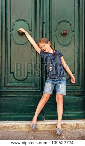 Fashion portrait of a cute little girl, wearing blue stripe t-shirt, denim shorts and grey shoes, standing next to old green door