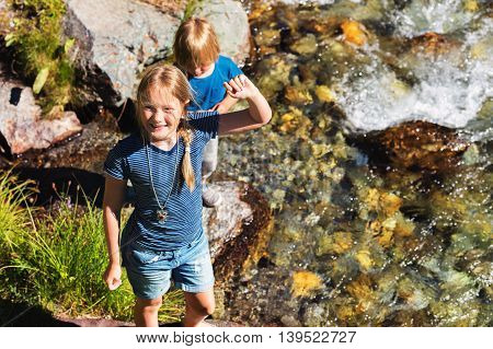Two cute kids playing by mountain river on a nice summer day, top view