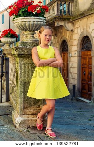 Outdoor fashion portrait of a cute little girl of 8-9 years old on the old street of Tuscany, Italy. Preteen kid wearing green dress, arms crossed, vertical image