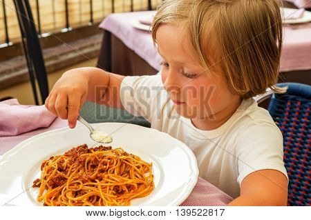 Adorable toddler boy eating spaghetti bolognese with cheese
