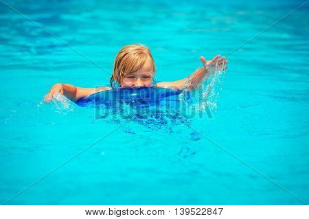 Happy little boy playing in swimming pool on a hot summer day
