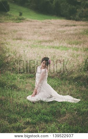 young beautiful  woman in white lacy dress sit on meadow summer day full body shot