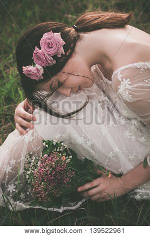 young beautiful  woman in white lacy dress hold bouquet of wild flowers sit  on meadow