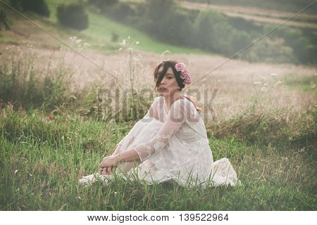 young beautiful  woman in white lacy dress sit  on meadow full body shot