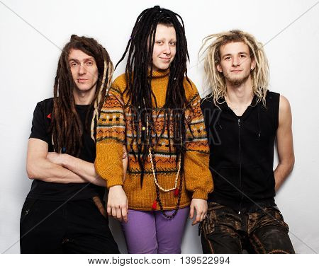Three young people, two boys and a girl, with dreadlocks are standing and smiling, white background