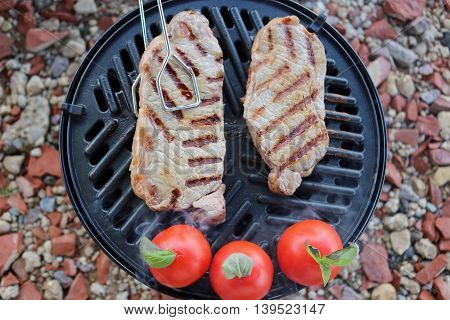 Two steaks on a barbeque just starting to cook. Three tomatoes with basil to the side.