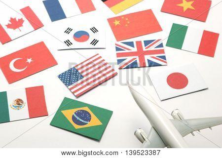 Travel by airplane. Miniature airplane go toward  national flags of many countries.