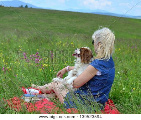 Blonde woman with her dog sitting on meadow surrounded with pink flowers and observing a landscape