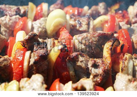 Meat and vegetables cook grilled macro on charcoal on a background of a smoke, close-up
