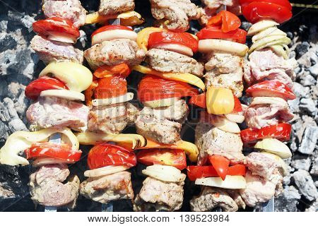 Cooking barbecue. Meat and vegetables tomato, bow, pepper, grilled on charcoal, close-up