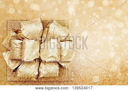 Beautiful golden gift against a bokeh background with copy space.