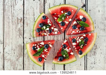 Watermelon Pizza In Slices With Blueberries, Mint, Balsamic Glaze And Feta, Above View On Rustic Whi