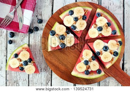 Sliced, Juicy Watermelon Pizza With Bananas, Blueberries, Nuts And Yogurt, Above View On Wood Servin