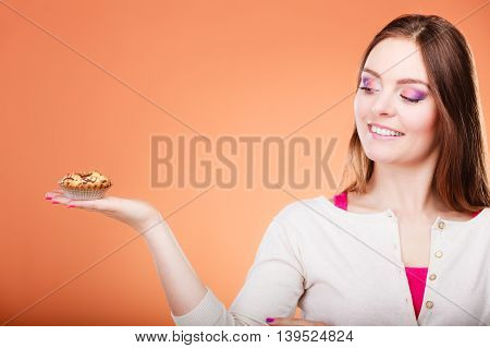 Bakery sweet food and people concept. Smiling woman holds cake cupcake in hand orange background