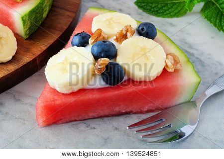 Slice Of Watermelon Pizza With Bananas, Blueberries, Nuts And Yogurt, Close Up On Marble