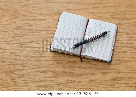 A pen on top of a blank notebook.
