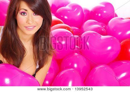 Hermosa chica sobre fondo de globos rosa