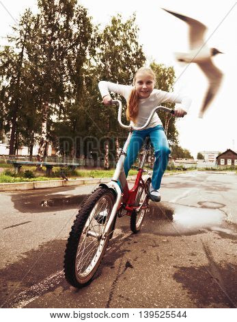 Young girl is cycling rides through a puddle in the park, and a seagull flying past.