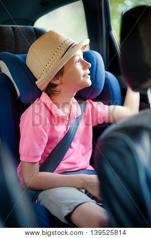 Little boy sits in the safety seat in car