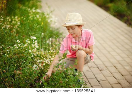 boy sitting in the flowers in the spring time