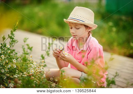 boy sitting in the flowers in the summer