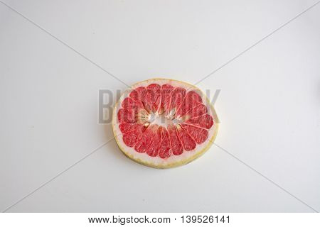 One Slice Of Red Pomelo On A Light Background