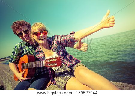Happy young man hipster with guitar and woman giving thumb up by sea ocean. Handsome guy and pretty girl in sunglasses relaxing on summer vacation.