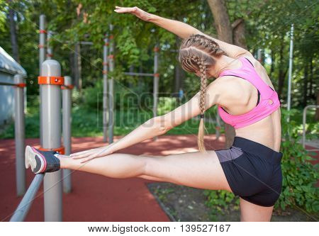 Sportswoman In Sportswear Stretching Legs On Sports Bars, Outdoor