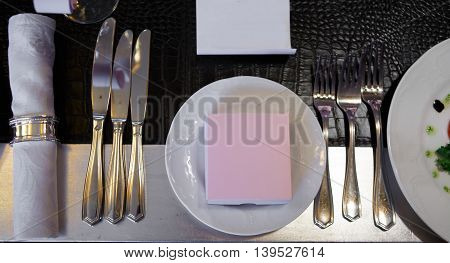 Decorated table with dishes on a Banquet table covered in crocodile skin. Glasses and plates, forks and knives, napkins and buttons for a luxurious evening celebration. Luxury festive table.