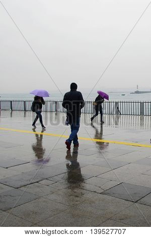 Istanbul Turkey - April 18 2014: Rain in Istanbul People are trying to reach the ferry pier in Kadikoy.