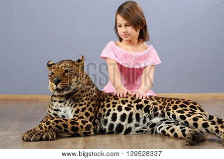 Girl child sits near beautiful leopard on wooden floor in grey studio