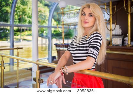 Blonde pretty woman in striped t-shirt stands near bar and window on ship