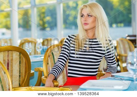 Blonde pretty woman in striped t-shirt sits at table and looks away in restaurant