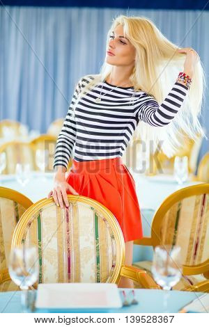 Blonde pretty woman in striped t-shirt corrects hair in restaurant