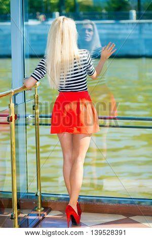 Blonde pretty woman in striped t-shirt sits near big window on ship, back view