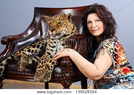 Middle-aged woman in dress poses near beautiful leopard on armchair in grey studio