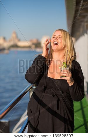 Young woman in black stands with cocktail and laughs on ship deck during sailing in city