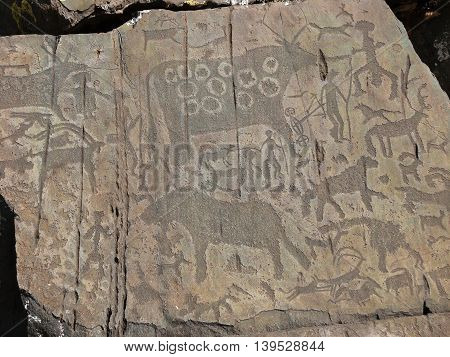 People and animals petroglyphs. Prehistorical petroglyphs carved in rocks. Siberian Altai Mountains Russia