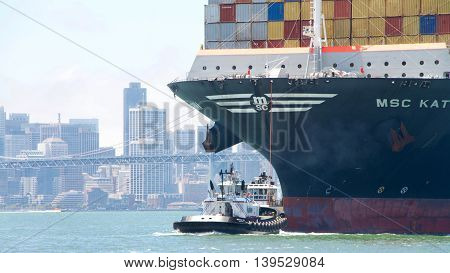 Oakland CA - July 18 2016: Tugboats powerful for their size assist MSC KATRINA manuever through the San Francisco Bay to the Port of Oakland. City of San Francisco in the background.