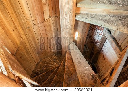 Old spiral staircase made of wood in an abandoned belfry