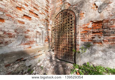 Ancient iron door decorated with wrought-iron details. Entrance to the abandoned russian church