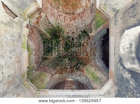 The old vault of the dome of an abandoned temple to sprinkle the plaster and moss-grown